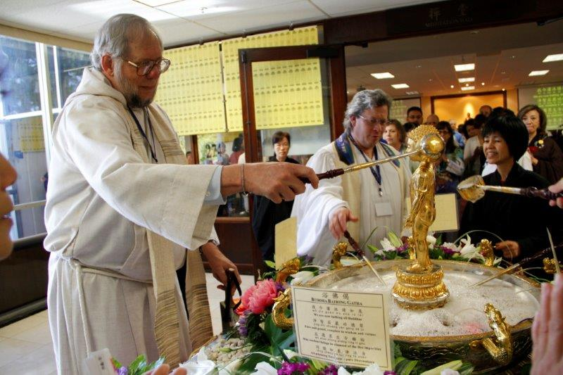 "Andrew Kille, left, takes part in a ""Bathing the Buddha"" ceremony"